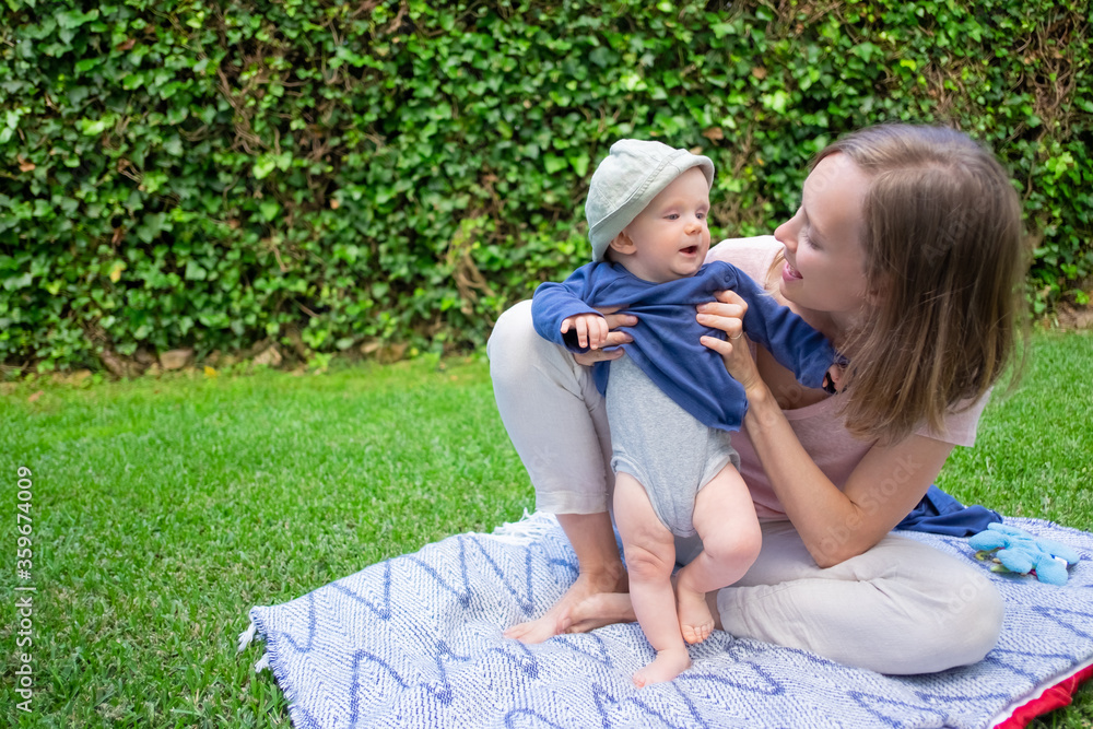 Fototapeta Beautiful mom playing with daughter in garden, talking with her and smiling. Cute baby girl in blue shirt standing on plaid barefoot. Summer family time and fresh air concept