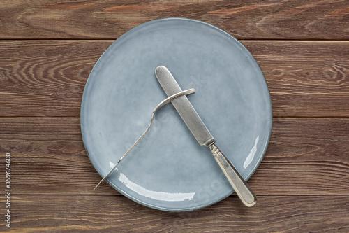 Obraz Talerz ceramiczny i sztućce na drewnianym blacie - fototapety do salonu