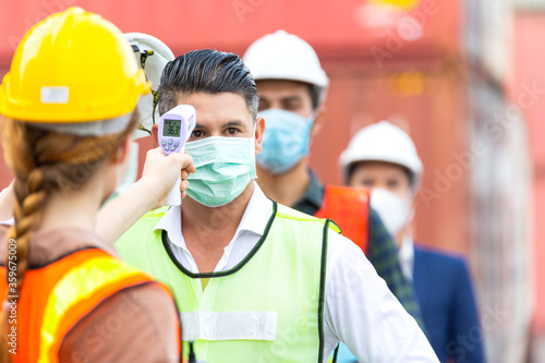 Female worker scanning fever temperature with digital thermometer to construction site staff wearing hygiene face mask protects from Coronavirus or COVID-19 Canvas Print