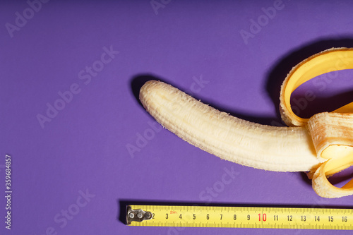 A banana is measured using a yellow ruler on a purple background Fototapeta