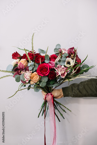 Very nice young woman holding beautiful blossoming bouquet of fresh roses, eucalyptus, cymbidium orchids, carnations, examine flowers in red and pink colors on the grey background © anastasianess