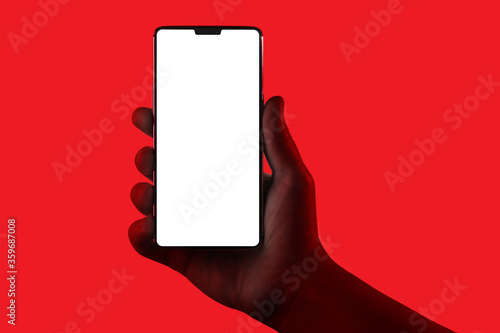 Hand holding phone. Silhouette of male hand holding smartphone isolated on red background. Bezel-less screen is cut with clipping path. © Sergey Peterman