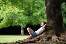 木陰でのんびりする女...
