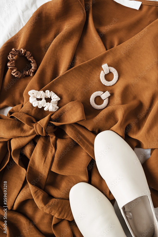 Fototapeta Fashion collage with women's clothes and accessories. Brown dress, white leather slippers, earrings. Minimal flat lay, top view lifestyle concept.