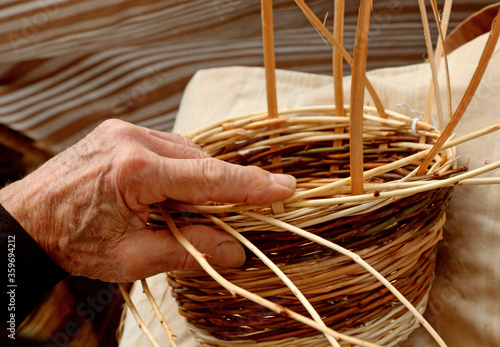 craftsman while he creates the wicker basket to sell it to the l Fototapeta