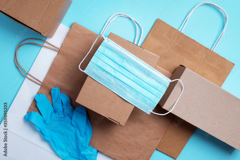 Fototapeta Craft paper cups, food box, gloves, bags, mask on blue background. Top view. Banner, copy space. Safe delivery, take away only concept. Food delivery service during coronavirus pandemic
