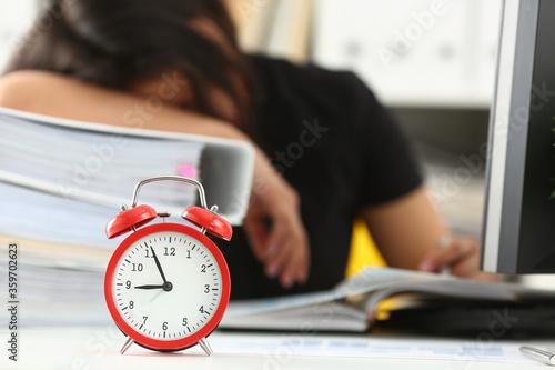 Fototapeta Close up of alarm clock and tired female worker taking nap on huge pile of document folders on blurred background obraz na płótnie