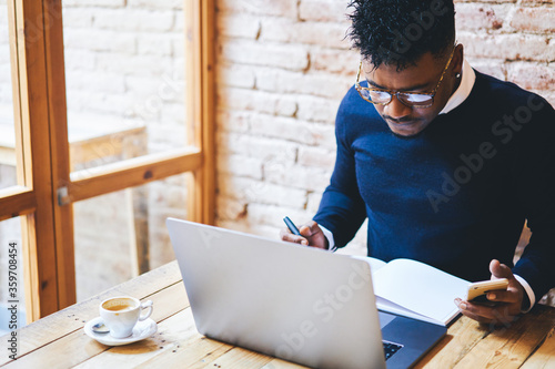 Fotografie, Tablou Concentrated afro american businessman working in coffee shop using modern devic