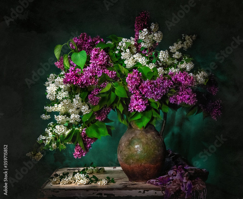 Foto Classic still life with bouquet of beautiful white and purple lilacss in old vintage jug in a ray of light on green background