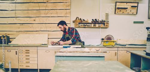 Fototapeta Bearded handsome cabinet maker at tabletop polishing wooden during working proce