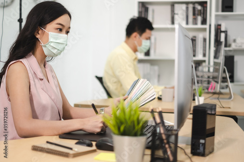 Fotografie, Obraz Business work in office with face mask social distancing quarantine during COVID