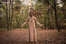 Woman In Vintage Dress In Autumn Forest Throwing Fall Leaves In Matching Color Palette