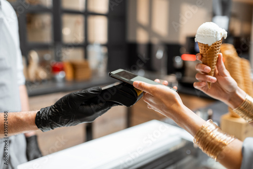 Seller makes contactless payment for a client in the ice cream shop, close-up Canvas