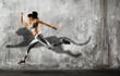 Leinwandbild Motiv Sporty young woman running on wall background