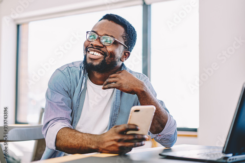 Fotografering Cheerful african american young male smiling holding mobile phone for checking new feed in social networks, happy dark skinned hipster guy looking away laughing at idea for publication in blog