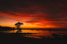 Orange Sunrise Between Clouds, Water And Trees