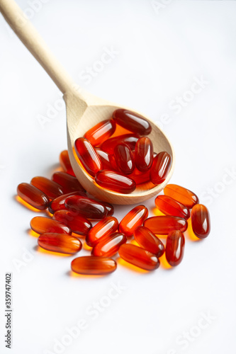 Valokuva wooden spoon with lecithin capsules on a light background