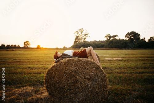 Carta da parati Stylish girl relaxing on hay bale in summer field in sunset