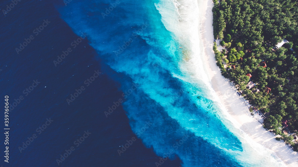 Fototapeta Top view aerial drone photo of stunning colored sea beach with crystalline water. incredibly beautiful blue ocean meet with powder-white seashore surrounded by tropical rainforest or palm trees jungle