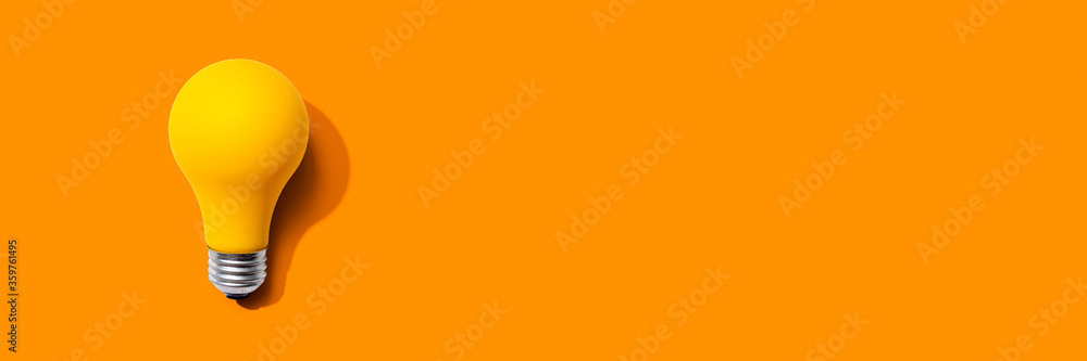 Fototapeta Yellow light bulb - flat lay from above