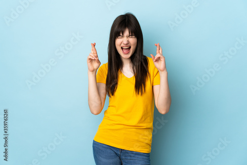 Valokuvatapetti Teenager Ukrainian girl isolated on blue background with fingers crossing