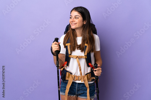 Fototapeta Young woman with backpack and trekking poles isolated on purple background looking to the side and smiling obraz