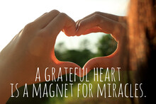 Inspirational Quote  - A Grateful Heart Is A Magnet For Miracles. With Young Woman Hands Making Love Sign Against The Sunset Light. Thankfulness And Gratefulness Inspiration Words Concept.