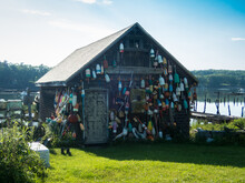 Wooden Fishing Shack Decorated With Lobster Buoys In Boothbay Harbor, Maine, On A Sunny Summer Day