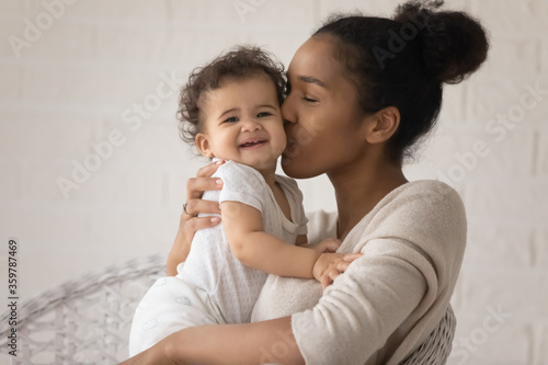 Photo Close up loving young African American mother kissing cute toddler daughter chee