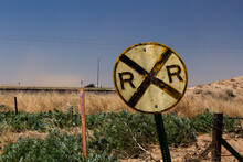 Battered Old Railroad Crossing Sign On A Country Road On The Prairie