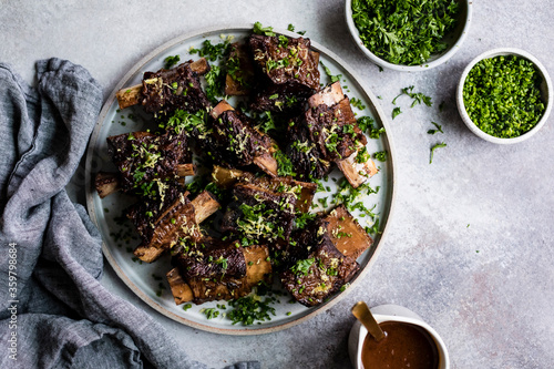 Roasted beef ribs with chopped parsley and chives on a plate. - 359798684
