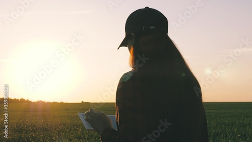 Fototapeta silhouette of female farmer with tablet studying wheat crop in field. close-up. agronomist girl works with tablet on wheat field in sun. business woman plans her income in field. grain harvest. obraz