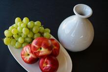 Summer Fruit Still Life With Fresh, Ripe Nectarines, Green Grapes, White Retro China, Black Background.