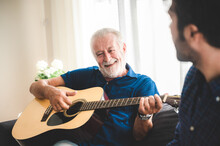 Happy Adult Son And Senior Father Playing Guitar On Sofa At Home Relaxing And Having Happy Time With Family
