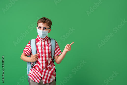 Photo schoolboy in protective mask, standing against background of a green Board
