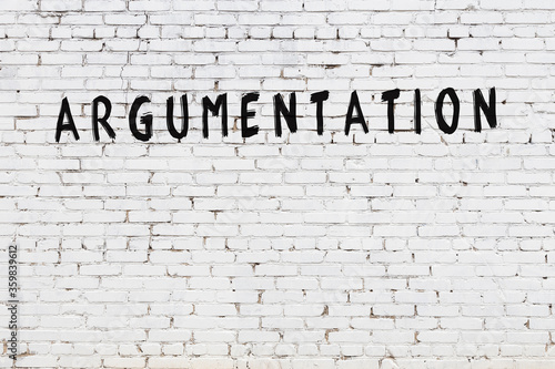 Word argumentation painted on white brick wall Canvas Print