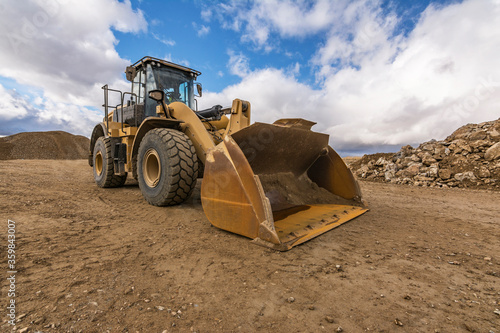 Cuadros en Lienzo Yellow excavator moving earth at a construction site