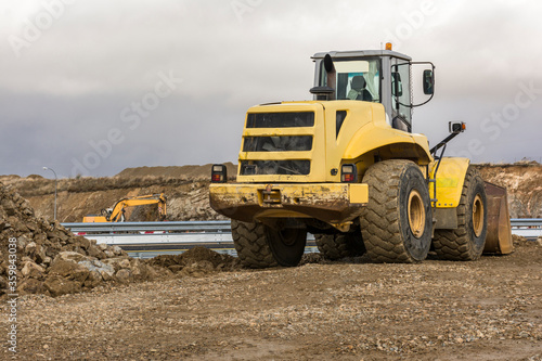 Fotografía Yellow excavator moving earth at a construction site