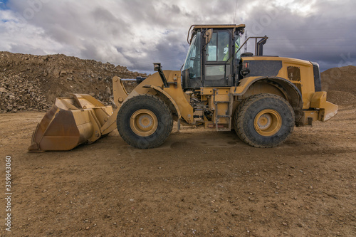 Fotomural Yellow excavator moving earth at a construction site