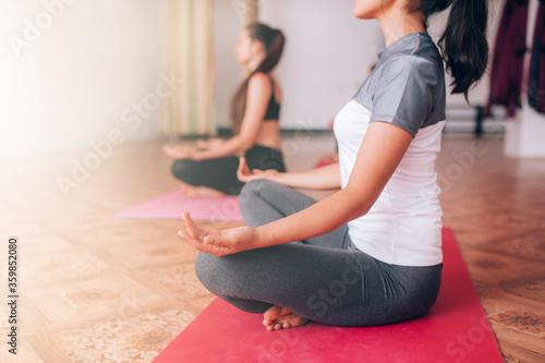 Fototapeta Beautiful young girls do yoga on rugs, relax, care about health obraz na płótnie