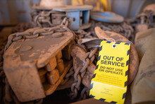 Safety Workplaces Yellow Out Of Service Tag Attached On Faulty Damage Defect Of Industry Heavy Duty Lifting Chains Block At Construction Site Perth, Australia