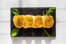 Croquettes With Yellow Sauce, Corn Salad And Arugula On Black Stone Plate At Sunny Kitchen. Top View On White Wooden Background. Traditional Spanish Snack