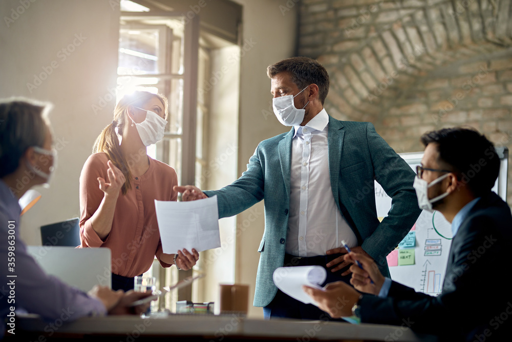 Fototapeta Business coworkers wearing protective face masks while having a meeting during COVID-19 epidemic.