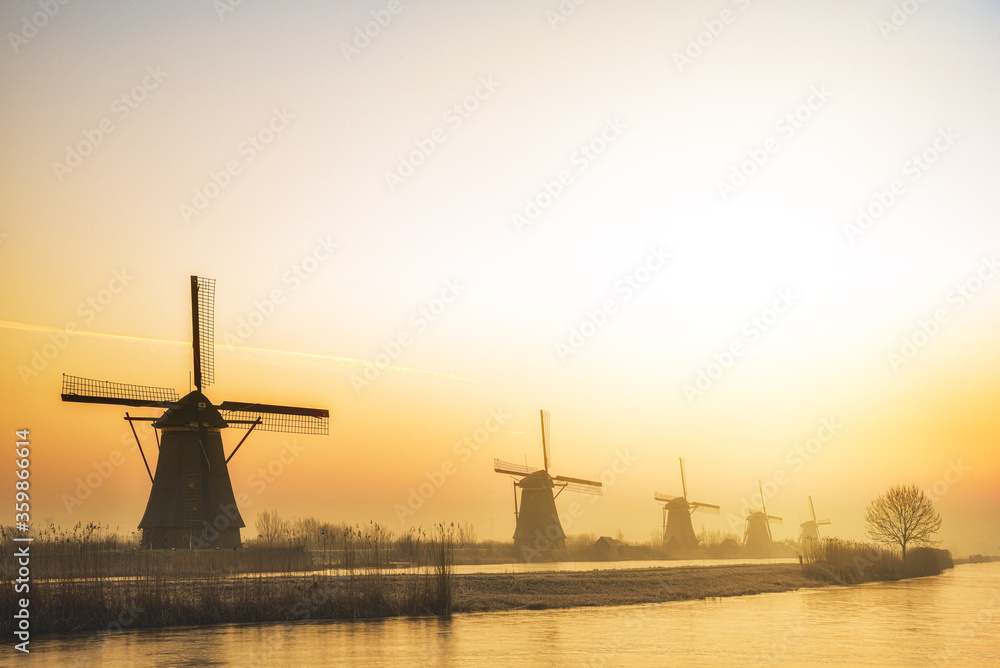 Alignement of five majestic windmills along a calm water canal at the gradient warm color sunrise in Alblasserdam, Netherlands