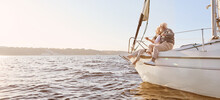 Explore Dreams. A Happy Senior Couple Sitting On The Side Of A Sail Boat On A Calm Blue Sea. Man Hugging His Woman While Enjoying View