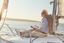Relaxed Senior Man Reading A Book, While Sitting On The Side Of Sail Boat Or Yacht Deck Floating In Sea