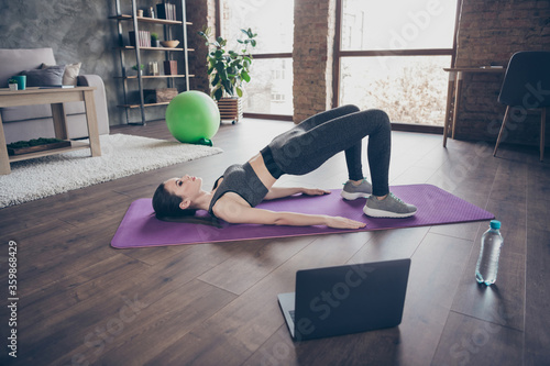 Top above high angle full body view photo athlete active energy girl have endurance intense practice watch video laptop do stretch abdomen stomach back plank on floor mat in house indoors