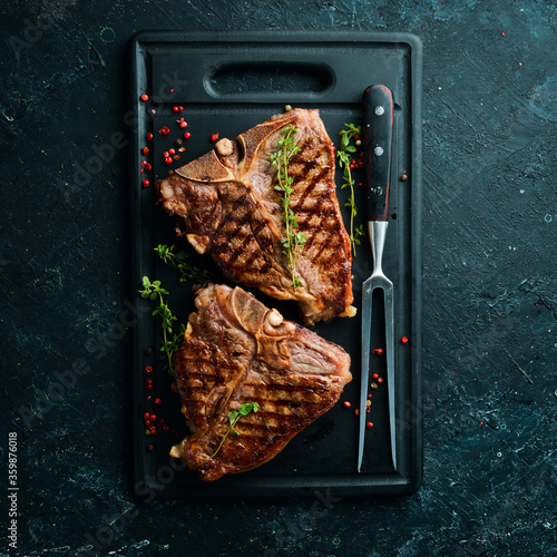 Fototapeta Two juicy grilled steaks with spices and herbs on a black background. Top view. Rustic style. obraz