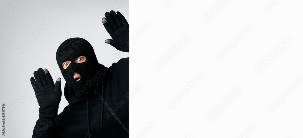 Fototapeta Masked thief with raised arms isolated on white wall