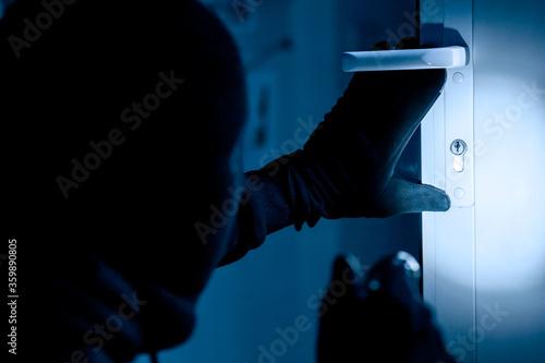 Fotografie, Obraz Thief in black balaclava cracking door with torch